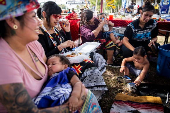 "From left to right, Dylanie Henry, Annie Washington, 10 months, Ruby Thomas, Joanie Henry, Moses Thomas, 8 months, Danelle Thomas, and Moses Thomas, 3, spend time together in their vendor booth where they sell beadwork and skirts during the 21st annual American Indian Arts Celebration on Friday, November 2, 2018, on the grounds of the Ah-Tah-Thi-Ki museum in the Big Cypress Seminole Indian Reservation. Dylanie Henry has been participating in cultural events as far back as she can remember, and now she is excited to share that experience with her daughter. ""It makes it special,"" she said."
