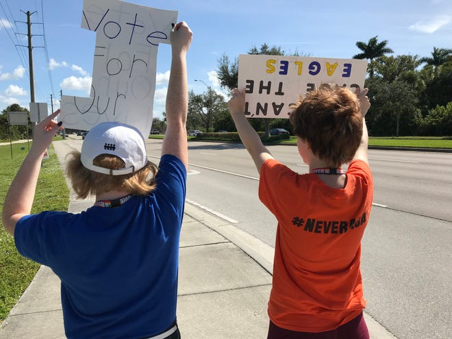 Michaela O'Brien, left, and Serenidy Alvey, both students at Naples High School, hold up a signs during an Election Day student walkout at Freedom Park in Naples on Tuesday, Nov. 6, 2018.