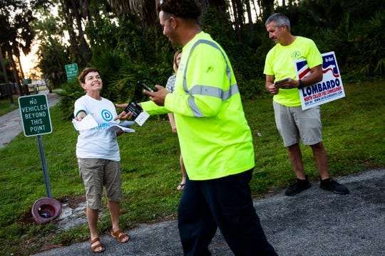 Nancy Menaldi-Scanlan, left, and Jeff Morse hand out leaflets to voters for their respective parties at Veterans Community Park in North Naples on Tuesday, Nov. 6, 2018.