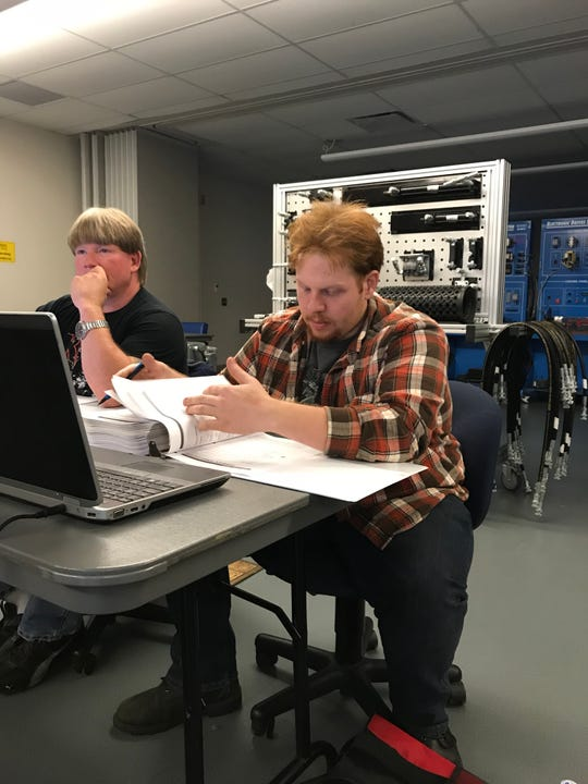 Travis Echols, right, looks at class material during a class for his multi-craft maintenance program at the Career and Technology Education Centers of Licking County. Echols received a scholarship for students in skilled trades that allows him to finish is program with little debt.