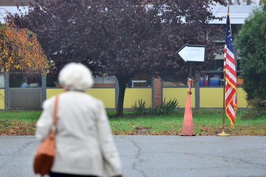 A voter walks toward the sign, which points voters to the polling area at Ryerson School at 30 McClelland Avenue in Wayne on Tuesday morning November 6, 2018.