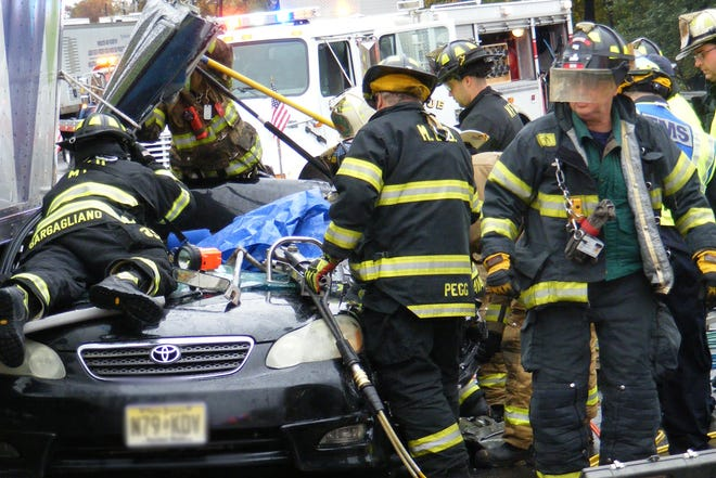 Firefighters from Rochelle Park, Maywood, and Hackensack work to free a victim who was entrapped in his Toyota Corolla following a multi vehicle crash on Route 17 northbound in Rochelle Park on Tuesday afternoon.