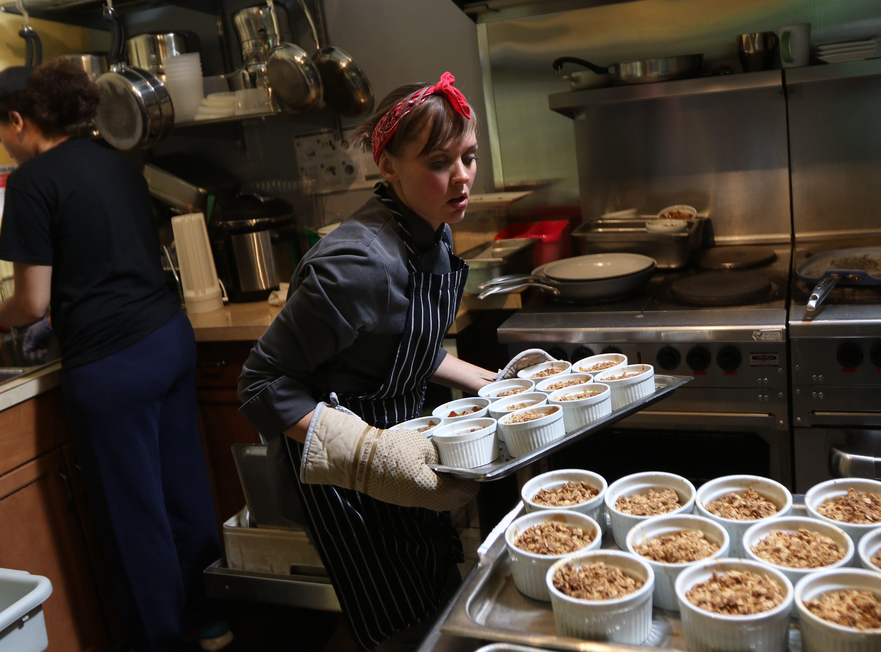 Sally Owens removes her pear and apple crumble from the oven in a crowded Montclair kitchen.  Owens says a pop-up dinner is stressful for her but also provides a positive shot of adrenaline. Wednesday, October 17, 2018.