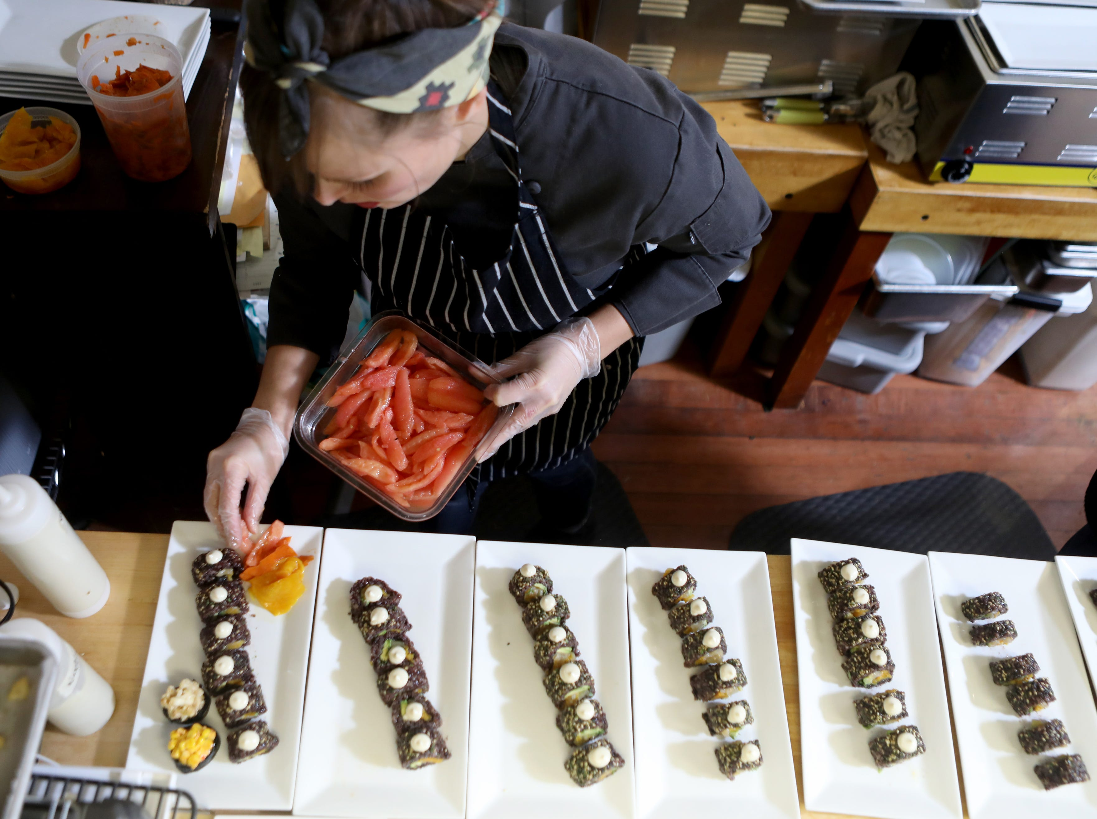 Sally Owens puts the finishing touches on her vegan maki roll, sashimi and gunkan maki.