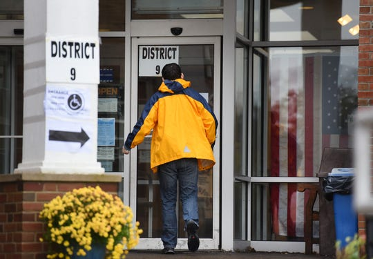 A man walks toward the entrance of Ridgewood Library where a polling area is provided on 11/06/18.