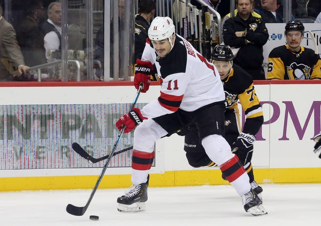 New Jersey Devils center Brian Boyle (11) moves the puck against Pittsburgh Penguins defenseman Jack Johnson (73) during the first period at PPG PAINTS Arena.