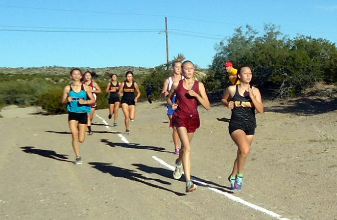 Freshman  Lady 'Cat Alexis Walker (cardinal) keeps an early pace with the pack during the District 3-6A Cross Country Championship Race in Alamogordo on Saturday.