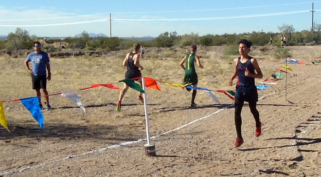 Freshman Wildcat Esau Au (right) reaches the finish line during the District 3-6A Cross Country Championship Race on Saturday in Alamogordo.