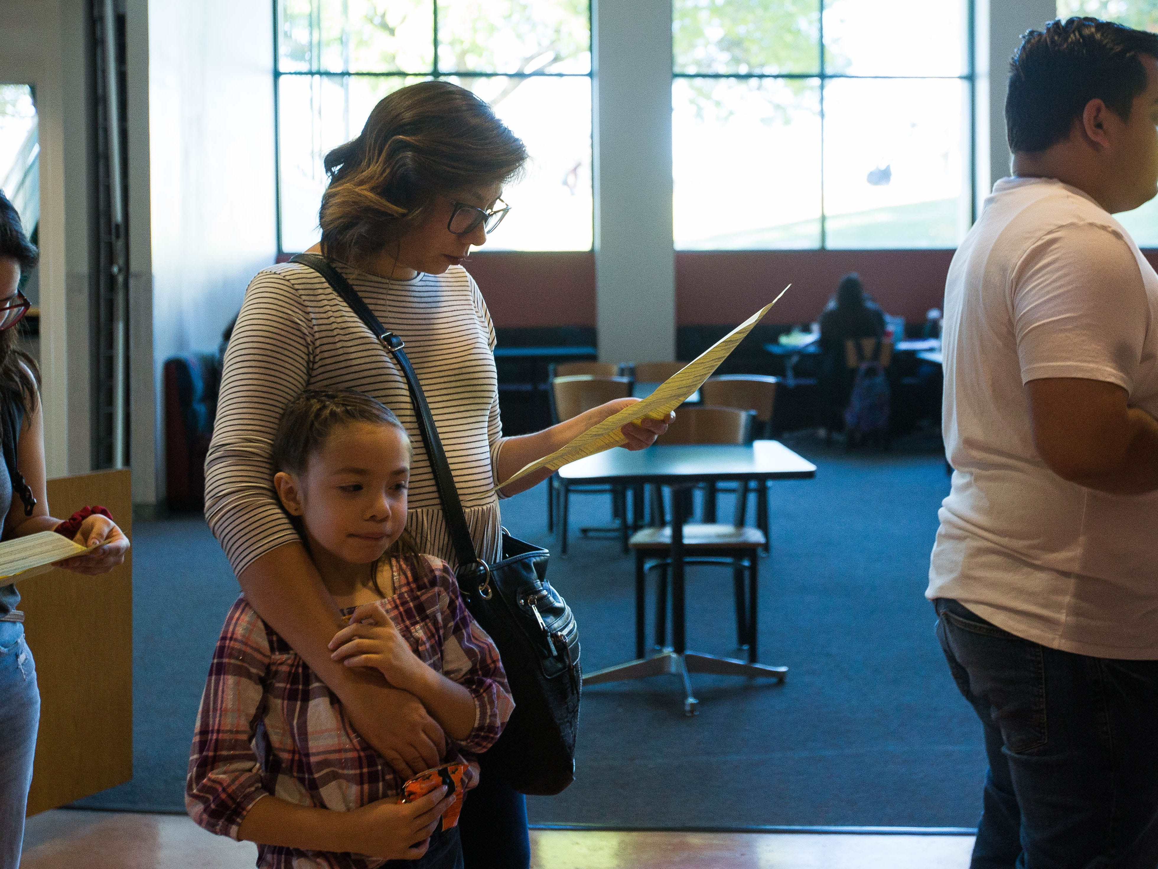 Cindy Moreno looks over a sample ballot as she waits with her daughter Mai Hemp, 6, in the line to vote at Corbett Center at New Mexico State University, Tuesday November 6, 2018. Moreno said her daughter was out of school and she brought her to the polling station to see what voting was all about.