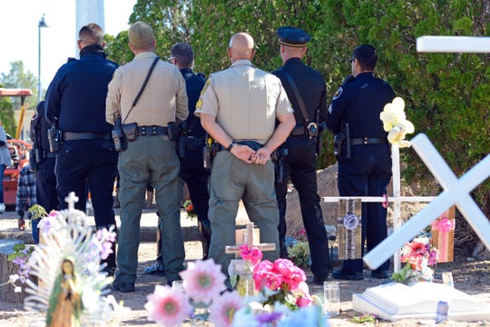 Law enforcement officers stand at a funeral for 24 people whose bodies were unclaimed Tuesday, Nov. 6, 2018, in Las Cruces.