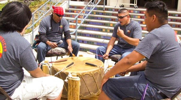 "Western New Mexico University alum, Lt. Bill ""Cody"" Ayon (second from the left), plays the drum he recently donated to the Smithsonian at a WNMU Native American Club event while he was a student."