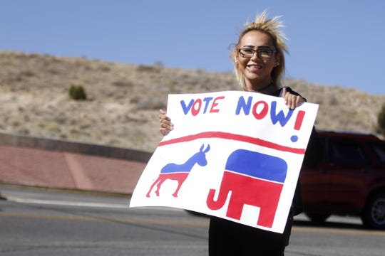 Student Kayla Moffitt, 18, encourages people to vote Tuesday near the Rocinante High School campus in Farmington.