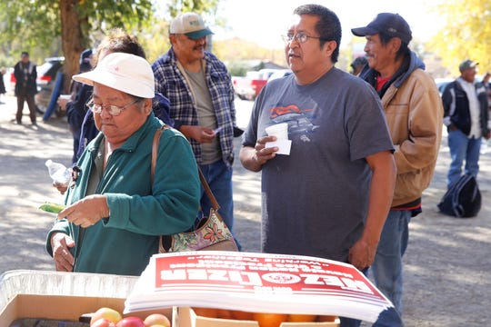 Shiprock Chapter voters wait on Tuesday to receive bananas, oranges and apples from the campaign stand for Navajo Nation presidential candidate Jonathan Nez and vice president candidate Myron Lizer.