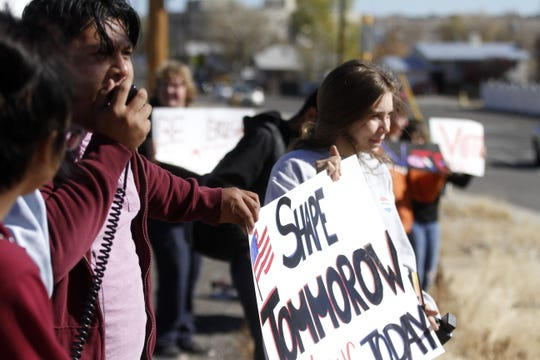 Rocinante High School students Alejandro Cruz and Emily Brozzo hold a sign encouraging people to vote Tuesday in Farmington.