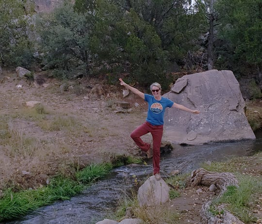 Anna Dozier shows off her talent of rock balancing while hiking on a trail.