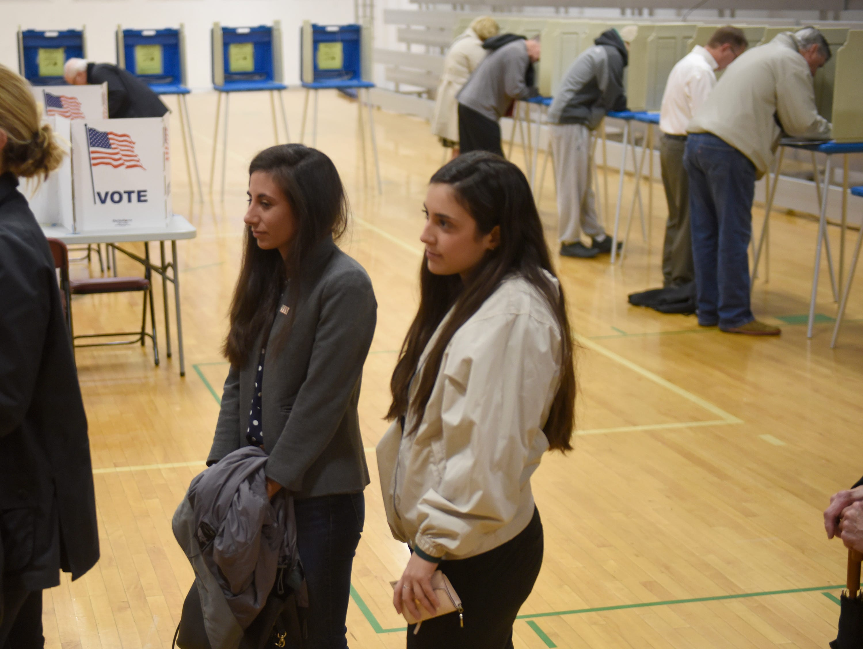 Mari Manoogian, Democrat candidate for state House District 40, and her sister Alis Manoogian wait in line to vote at Derby Middle School in Birmingham Nov. 6, 2018.