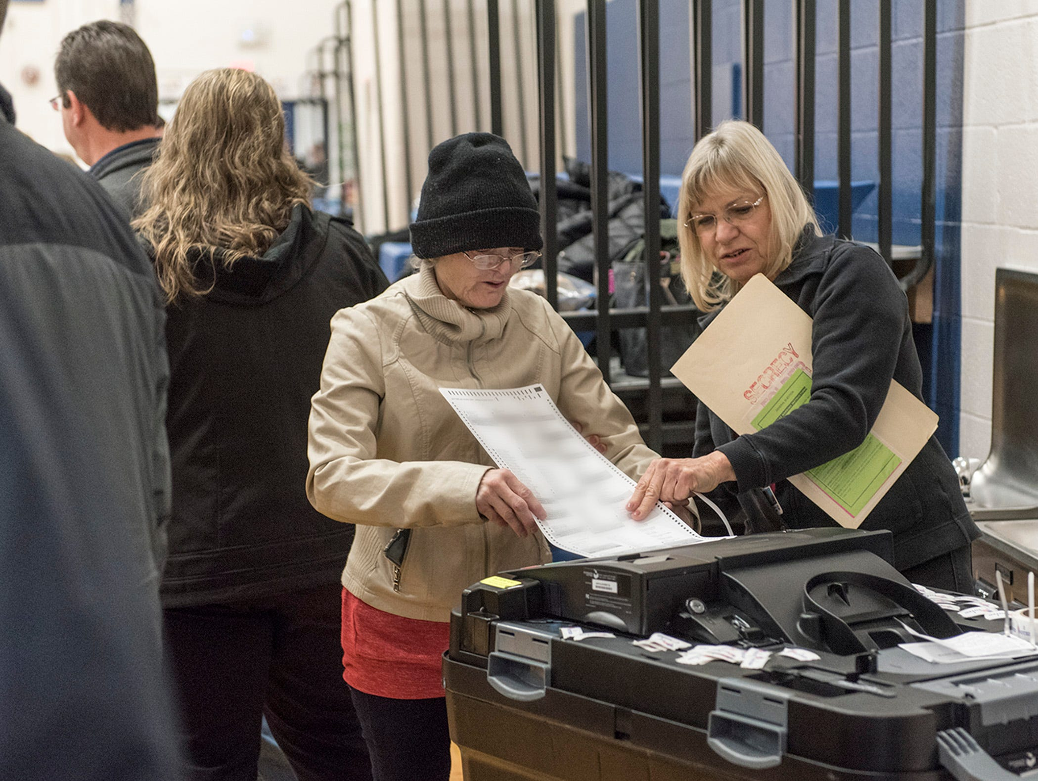 A voter feeds her ballot into a tabulating machine, with the help of an elections worker, at the Riley Upper Elementary School polling place in Livonia on Nov. 6. Problems with vote-counting machinery caused headaches and counting delays throughout Wayne County.