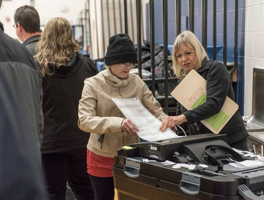 A voter feeds her ballot into a tabulating machine, with the help of an elections worker, at the Riley Upper Elementary School polling place in Livonia on Nov. 6 in this file photo.