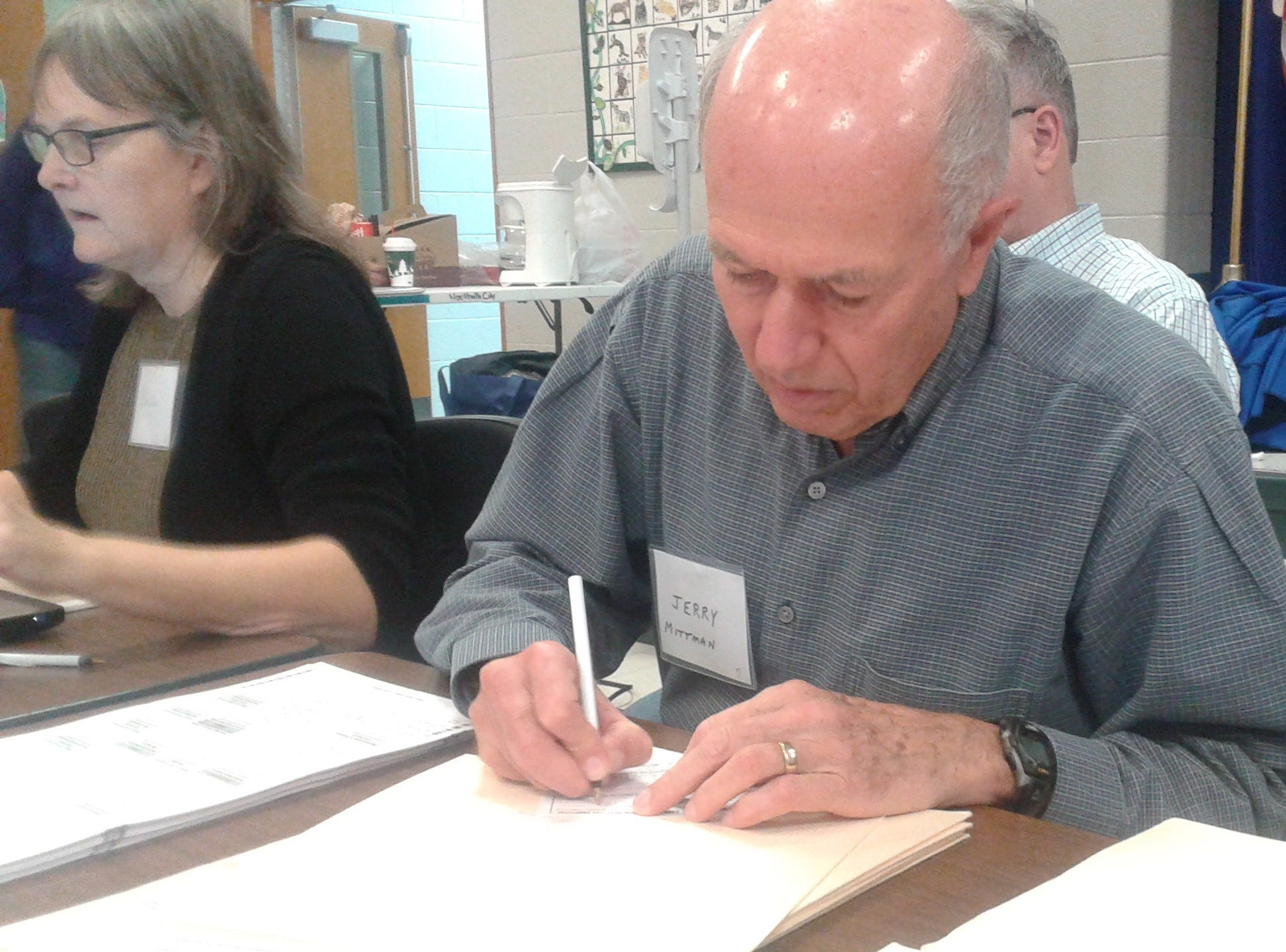 Precinct workers JoEllen Hyatt (left) and Jerry Mittman check in voters at Amerman Elementary School, precinct #2, in Northville.