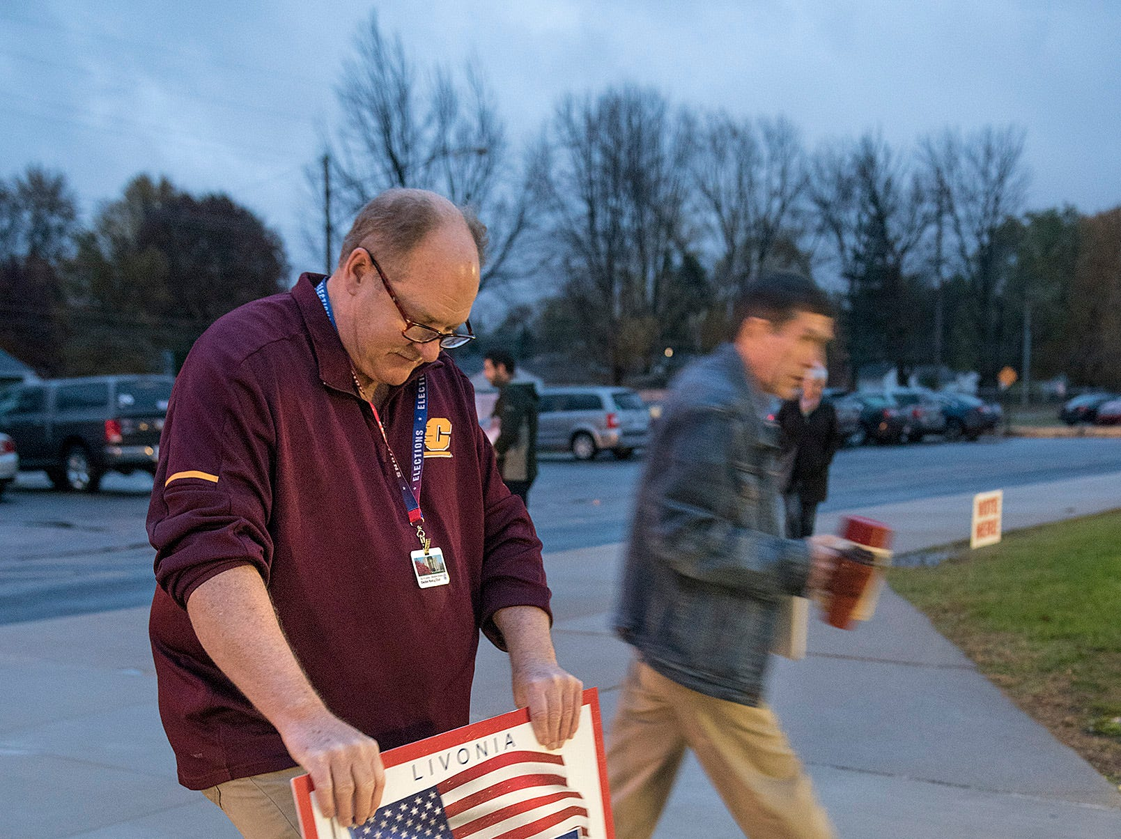 Robert Nash, husband of Livonia City Clerk Susan Nash, places signs in front of the entrance of Riley Upper Elementary School.