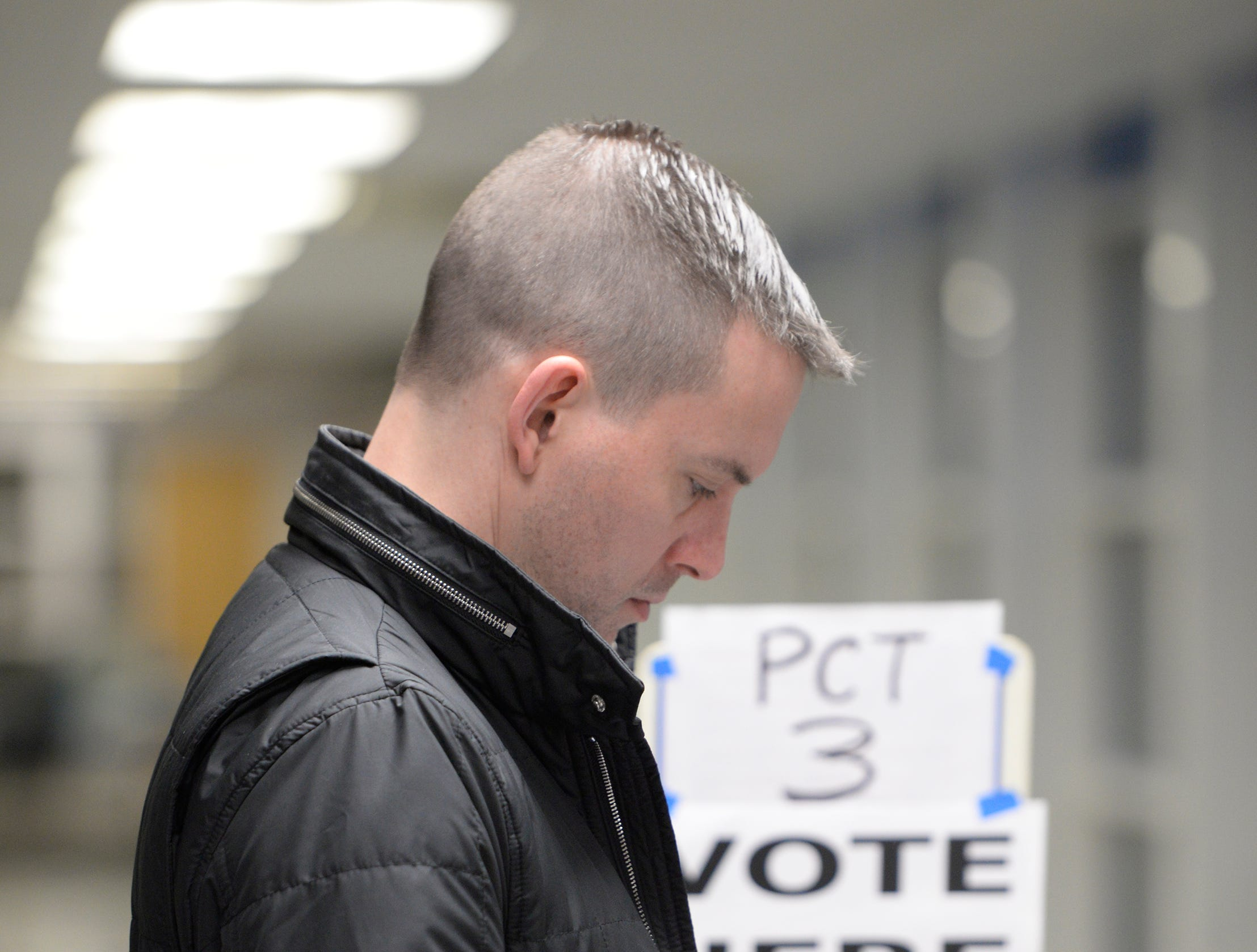 Chris Jacobson checks his phone while waiting in line to vote at Derby Middle School in Birmingham early on election day Nov. 6, 2018.