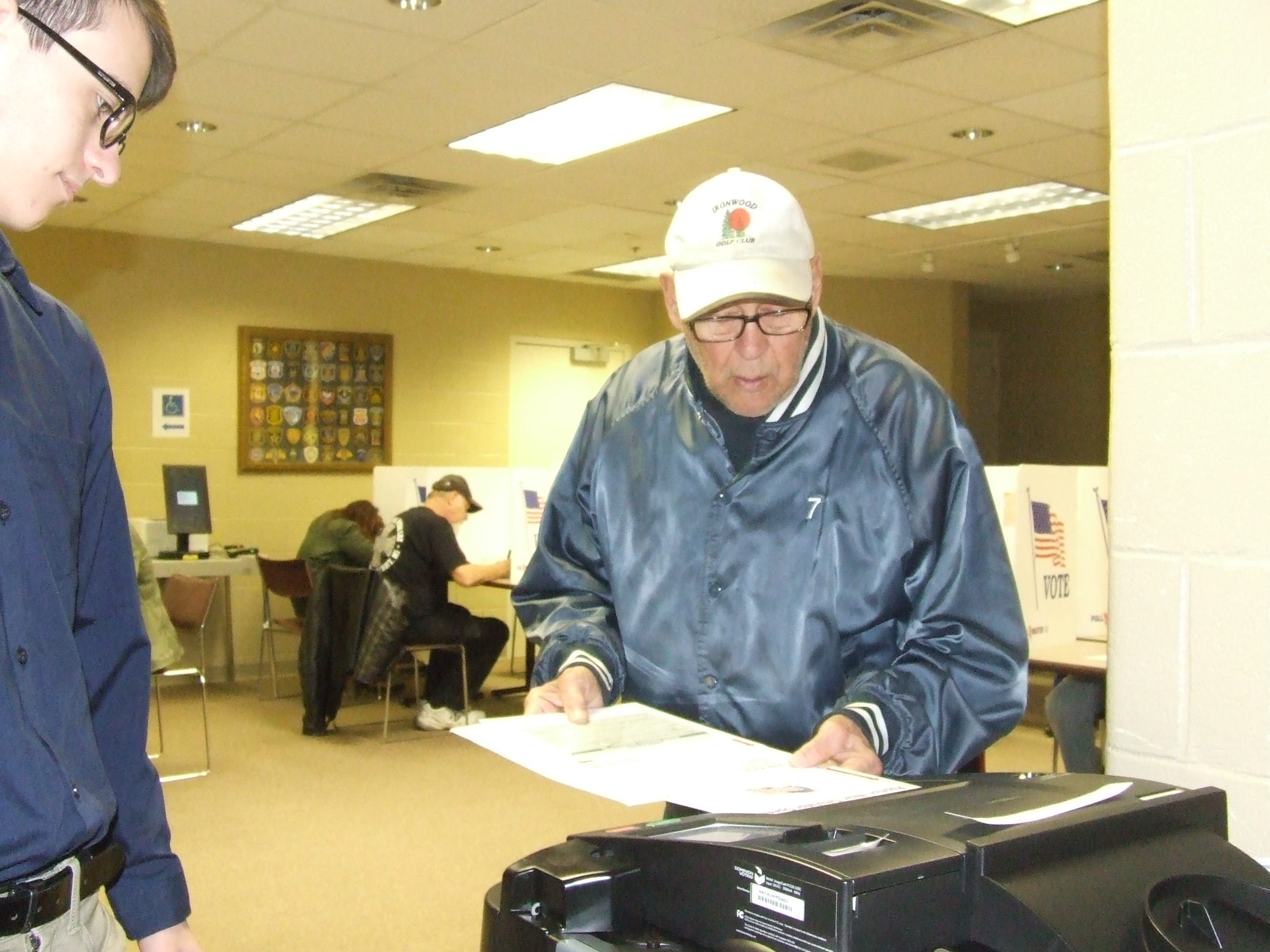 Robert Houff of Garden City feeds his ballot into the counting machine as first-time poll worker Zachary Litwalk looks on. Houff voted in Precinct 9 at the Garden City Police Department.