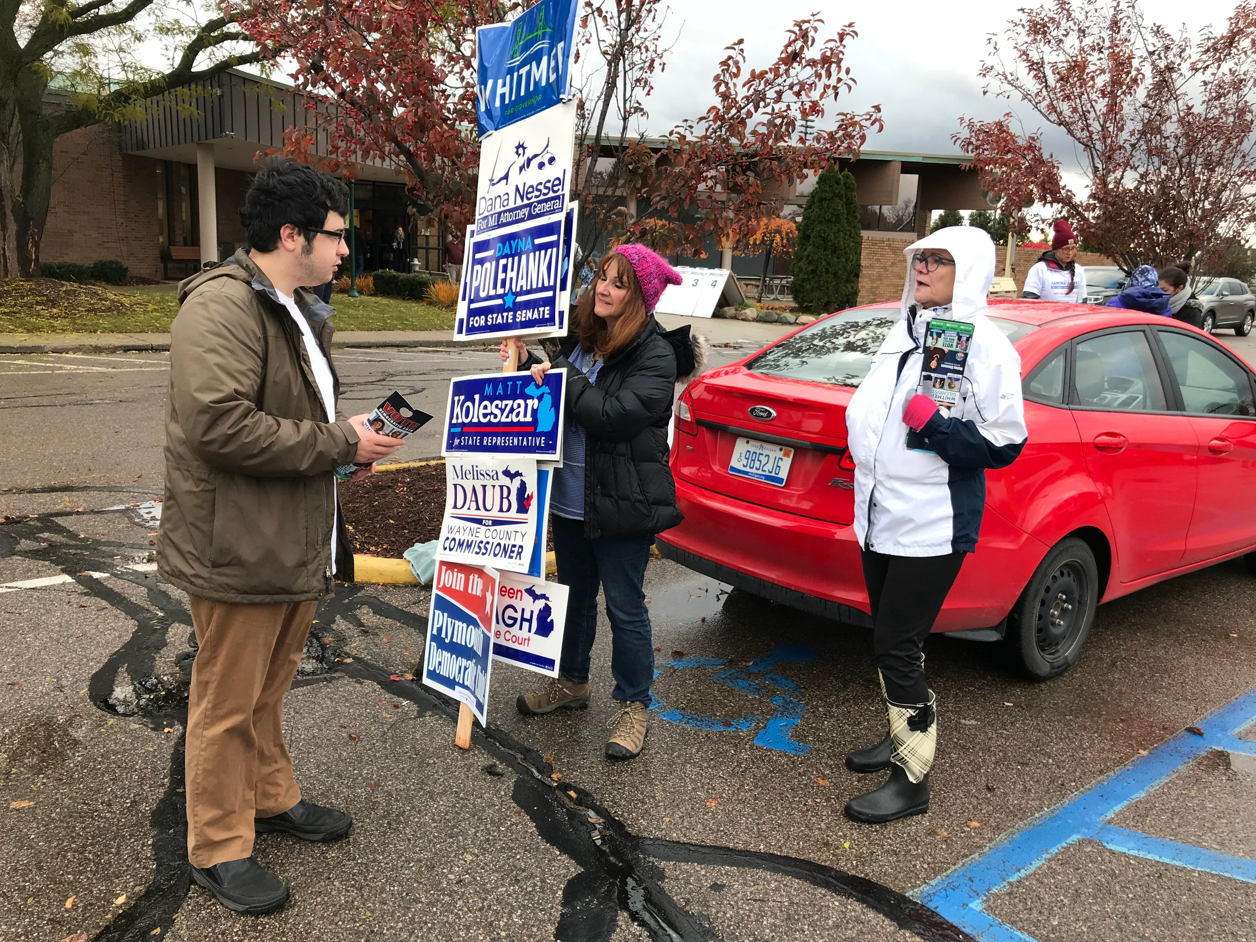 Campaign volunteers talk to voters outside the Plymouth Cultural Center.