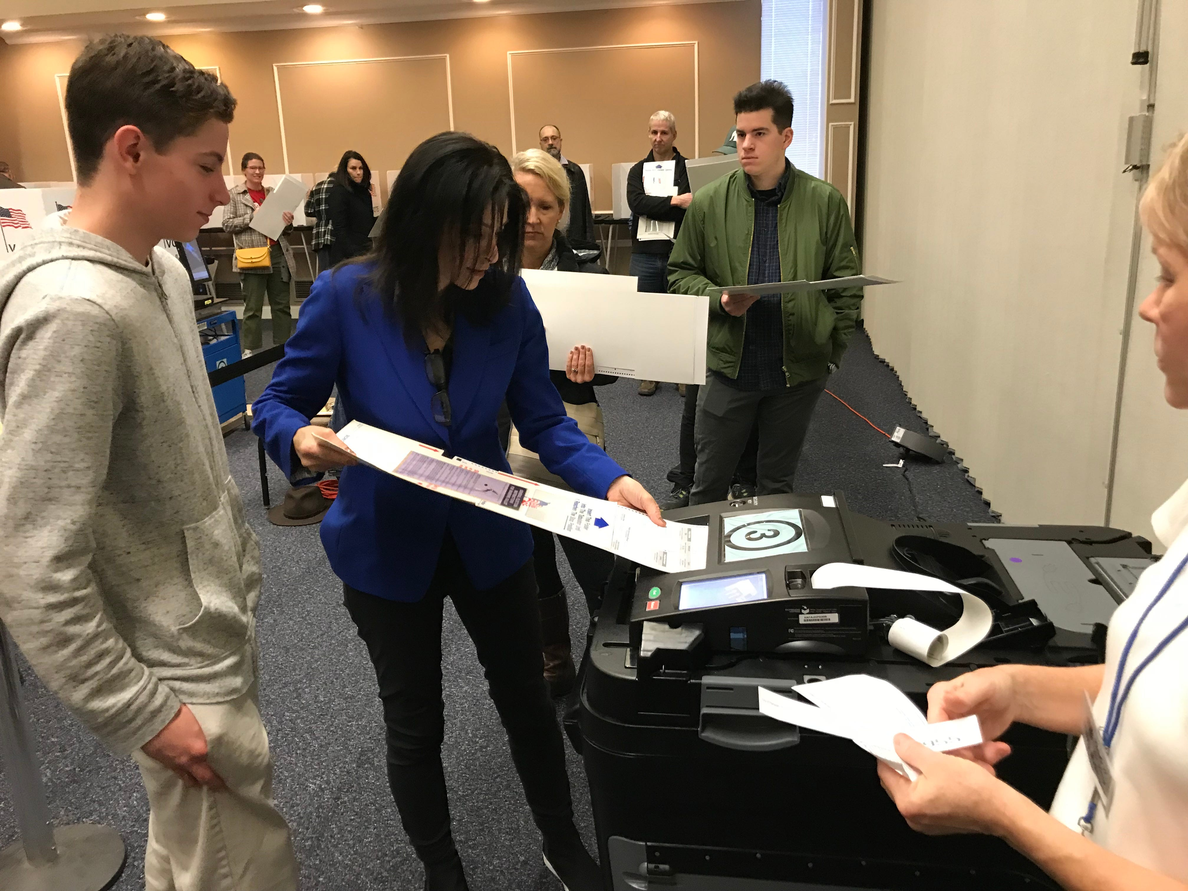 Michigan Attorney General candidate Dana Nessel casts her ballot at the Plymouth Cultural Center with a little help from her son, Zach.