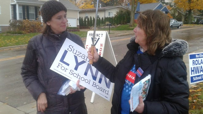 Kristin Gifford and Vicki Dwelley brave the rain to stump for their candidates at precinct #2 at Amerman Elementary School in Northville.