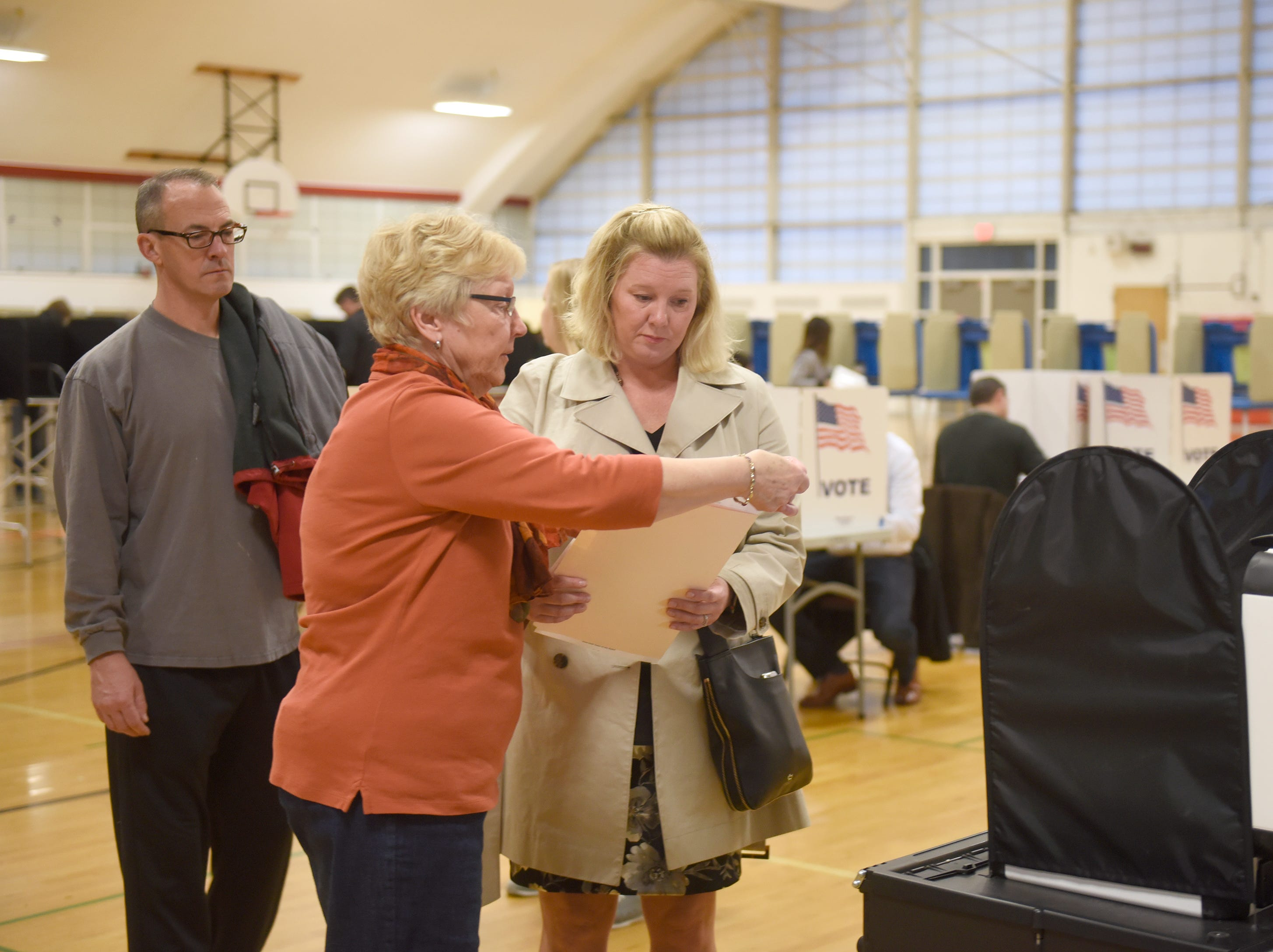Election worker Marty Logue helps Jeffery Clarke (left) and his wife Christine Whitaker-Clarke prepare to feed their ballots into the machine on election day Nov. 6, 2018 at Derby Middle School in Birmingham.