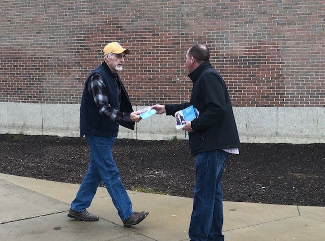 Scott Lyons hands out literature for state Senate candidate Dayna Polehanki at Grant Elementary in Livonia.