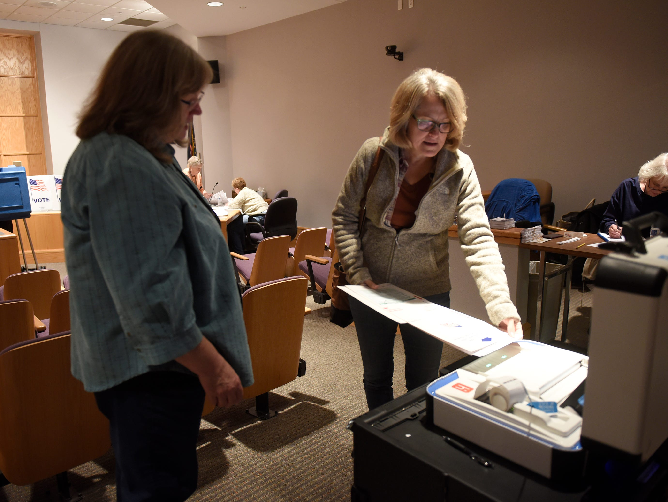 Precinct worker Marty Connell helps Julie Walker place her ballot in the counting machine at the South Lyon City Hall on election day Nov. 6, 2018.