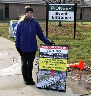 Mary Weidel stands next to her sign outside Pioneer Middle School urging voters to vote no on the PARC proposal.