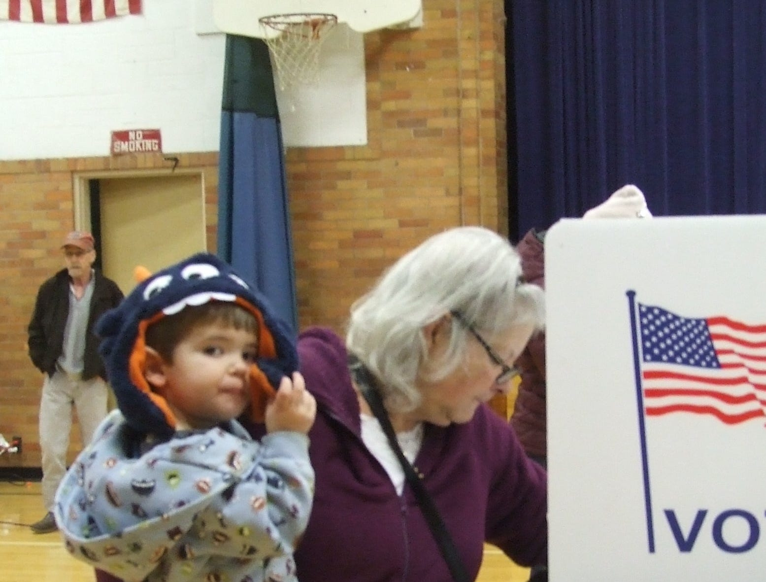 Terry Caloia of Redford Township votes at Hilbert Middle School on Tuesday while holding grandson Benjamin Lieto, 2.