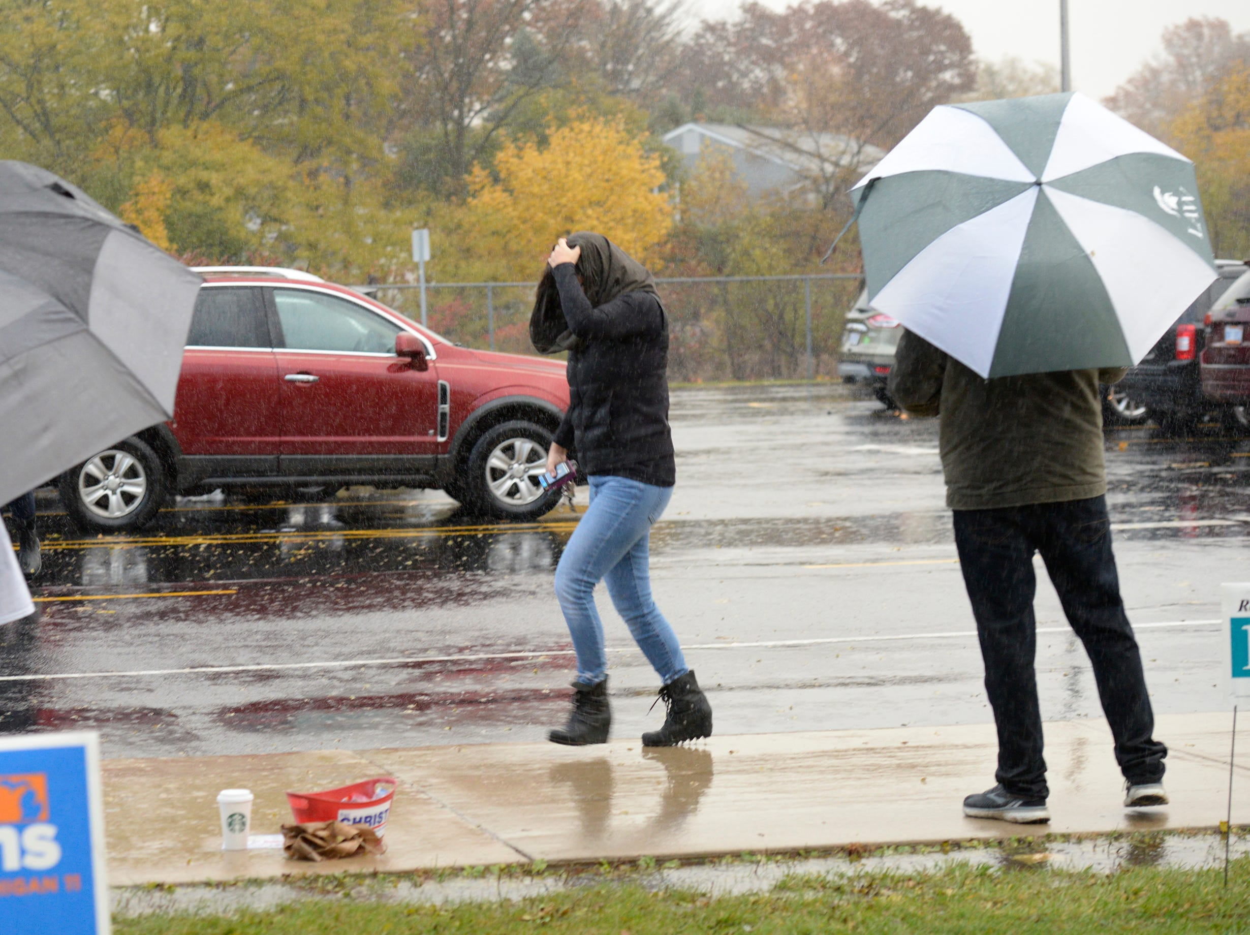 Voters dodge rain drips at Derby Middle School in Birmingham early on election day Nov. 6, 2018.