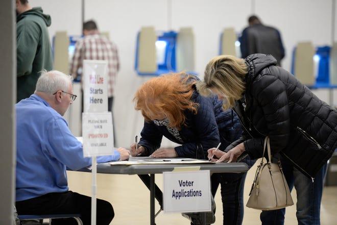 Precinct worker Robert Beals (left) checks in voters at Farmington High School on election day Nov. 6, 2018.