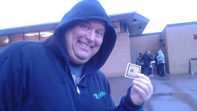 Adam Swallow shows off a sticker he received for voting at Northville's precinct #2 at Amerman Elementary School.