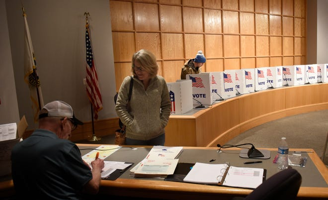 Julie Walker applies to vote at the South Lyon City Hall while John Schimpf finishes his ballot on election day Nov. 6, 2018.
