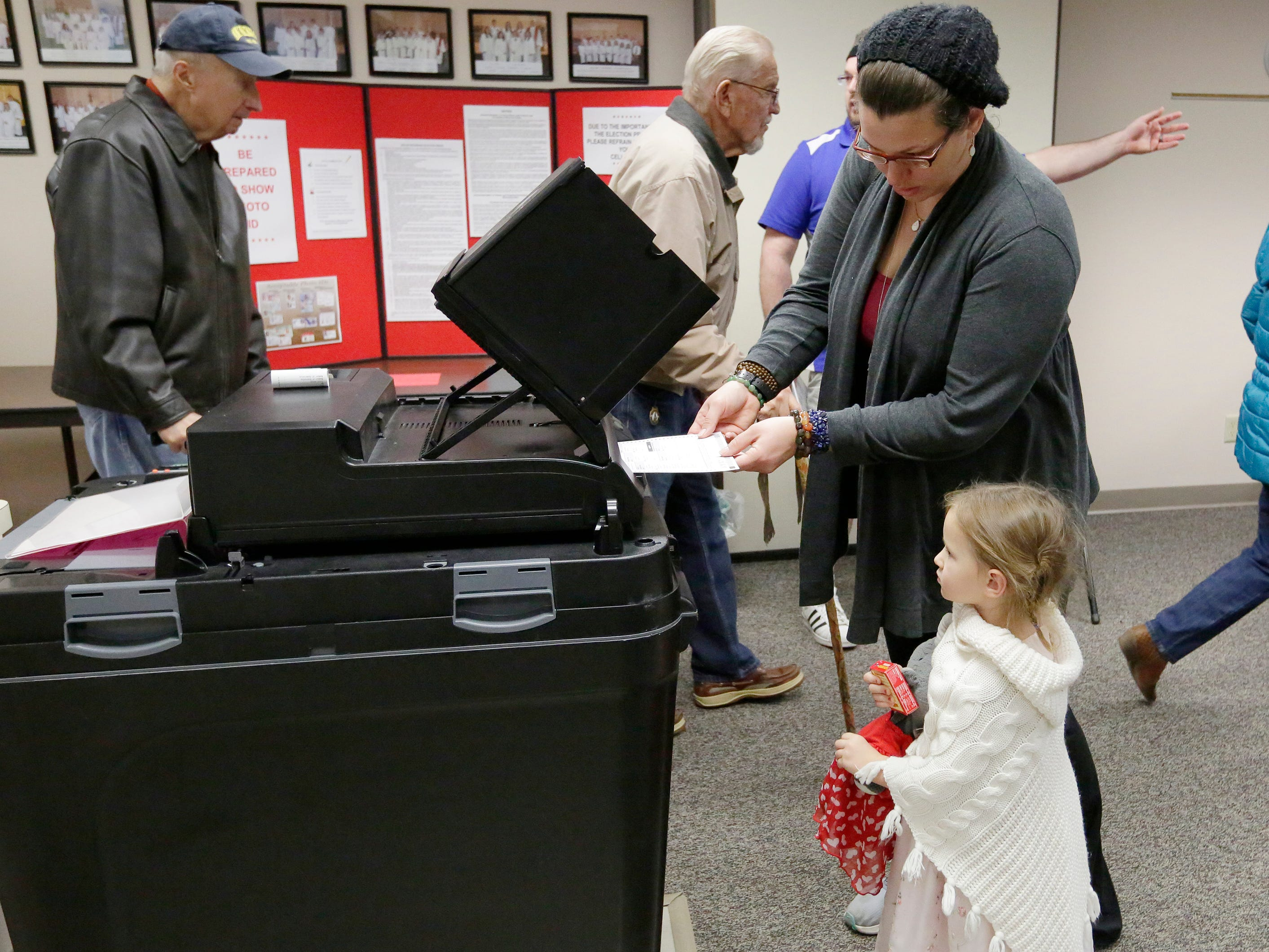 Jamie Mathieus inserts her ballot into the voting machine as her daughter Saphiera Ward watches at voting district 10 at Calvary Lutheran Church.  The mid-term voting kept poll workers busy as voters waited in lines at most polling stations in Oshkosh, Wis., Tuesday, November 6, 2018.  