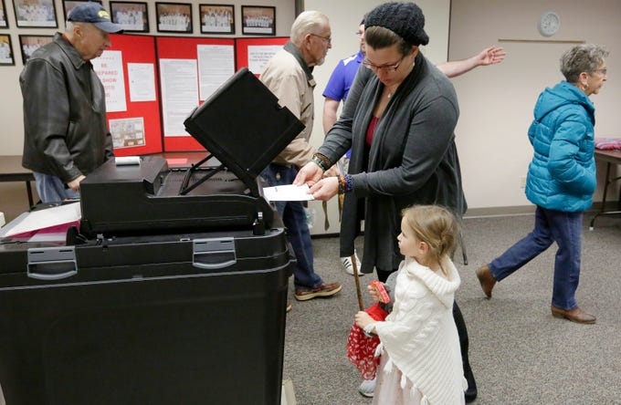 Jamie Mathieus inserts her ballot into the voting machine as her daughter Saphiera Ward watches at voting district 10 at Calvary Lutheran Church.  The mid-term voting kept poll workers busy as voters waited in lines at most polling stations in Oshkosh, Wis., Tuesday, November 6, 2018.  Joe Sienkiewicz/USA Today NETWORK-Wisconsin