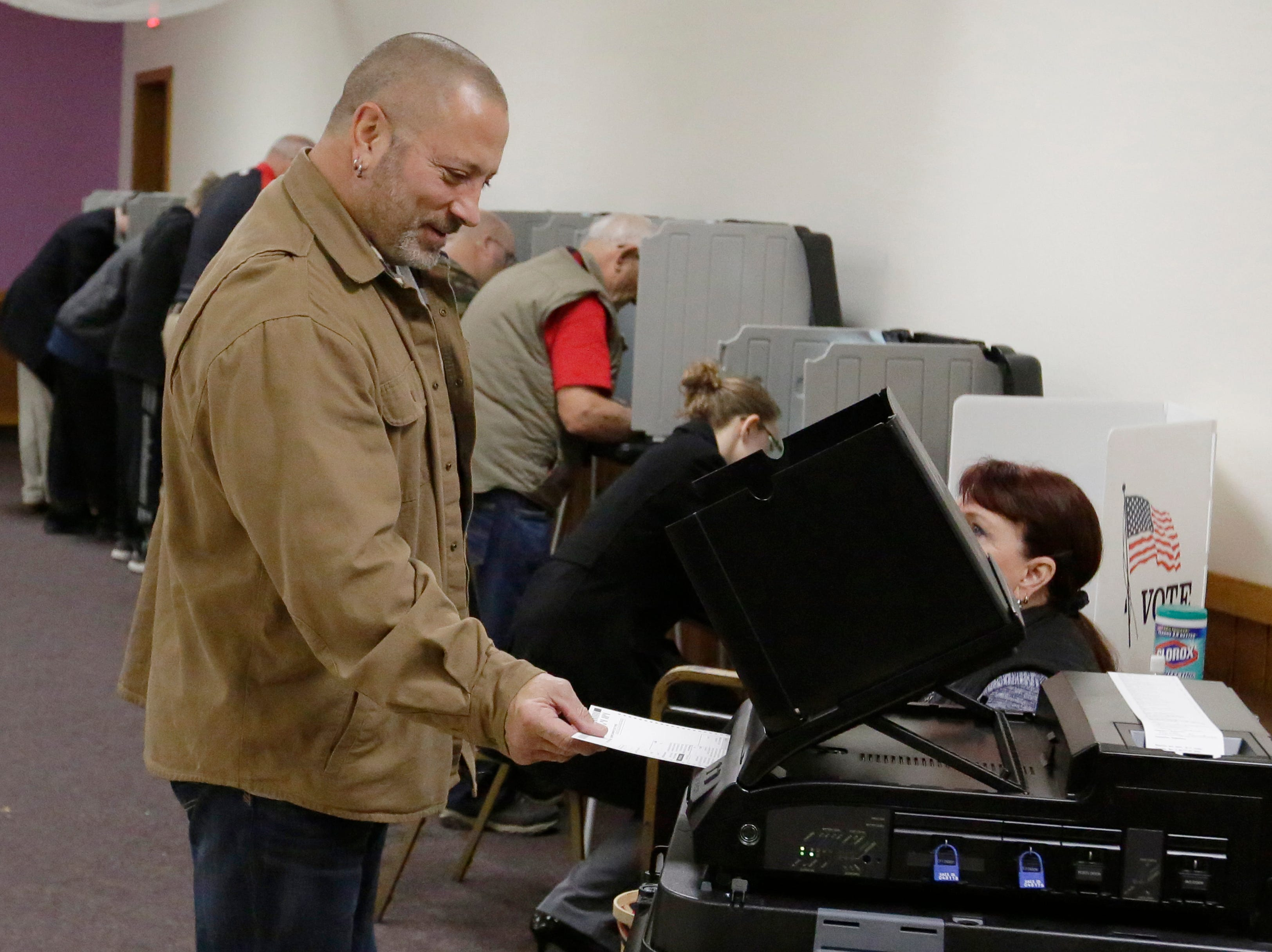 William Ranieri inserts his ballot into the voting machine at voting district 13 at the Oshkosh Elks Lodge.  The mid-term voting kept poll workers busy as voters waited in lines at most polling stations in Oshkosh, Wis., Tuesday, November 6, 2018.  