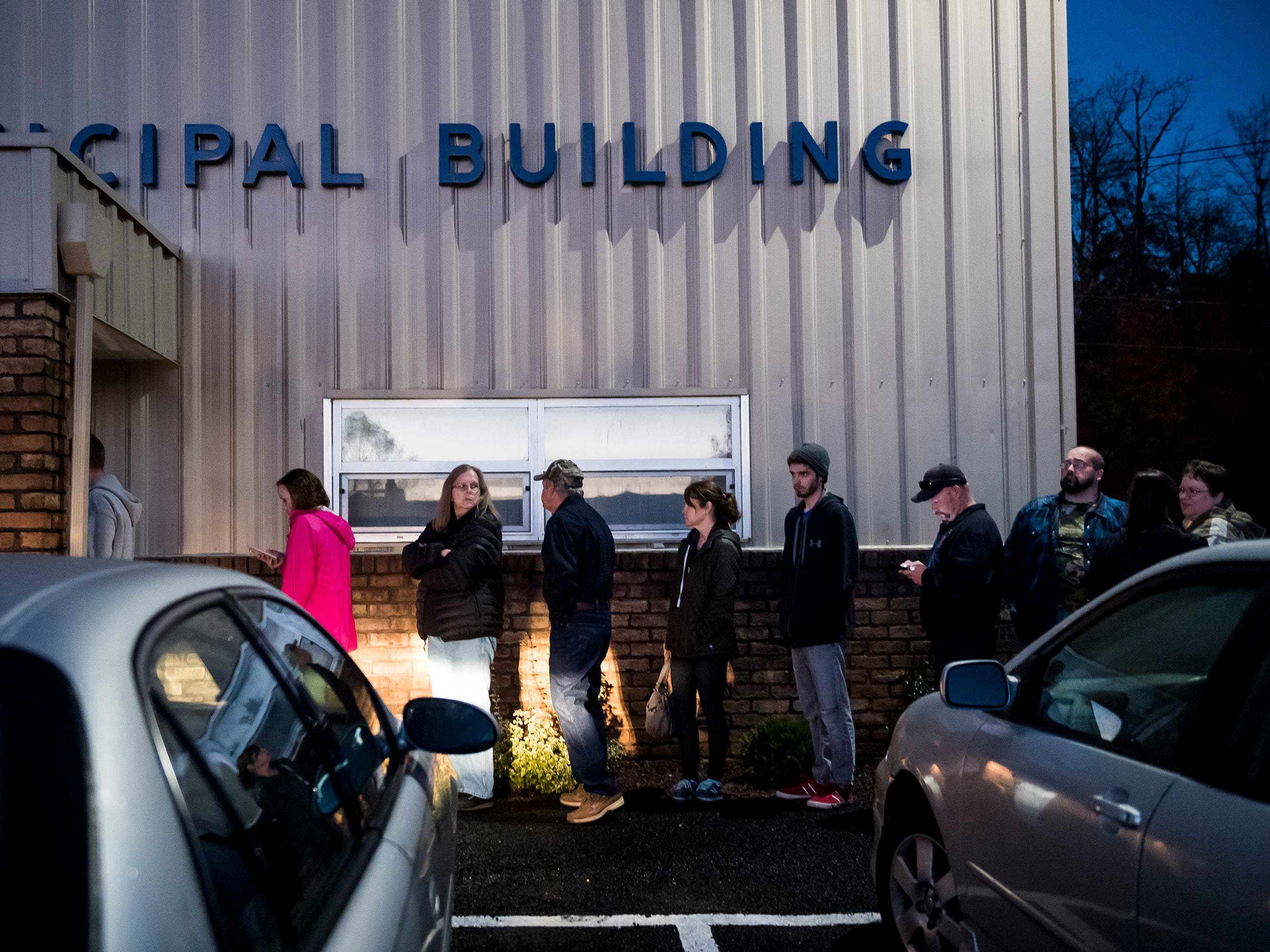 People stand in a line outside a polling station at the Oxford Township Municipal Building on Tuesday, November 6, 2018.