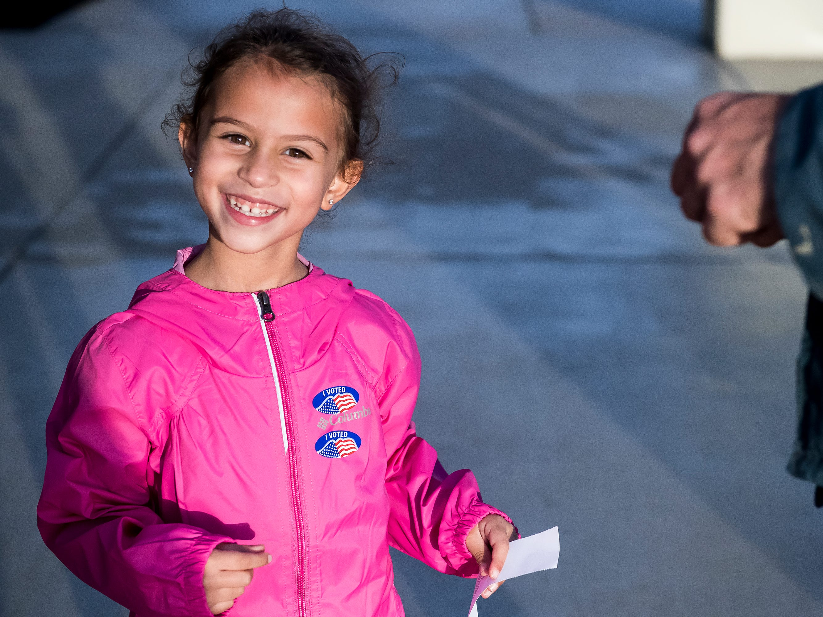Olivia Zions, 5, smiles after going to the polls with her father, Andrew Zions, at the Southeastern Adams Volunteer Emergency Services building in Conewago Township on Tuesday, November 6, 2018.