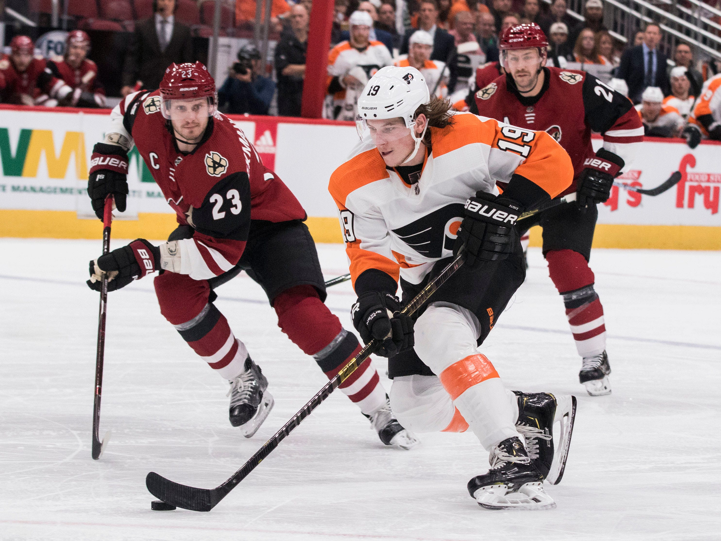 Philadelphia Flyers' Nolan Patrick (19) skates past the Arizona Coyotes' Oliver Ekman-Larsson (23) and Derek Stepan (21) during the first period of an NHL hockey game Monday, Nov. 5, 2018, in Glendale, Ariz. (AP Photo/Darryl Webb)