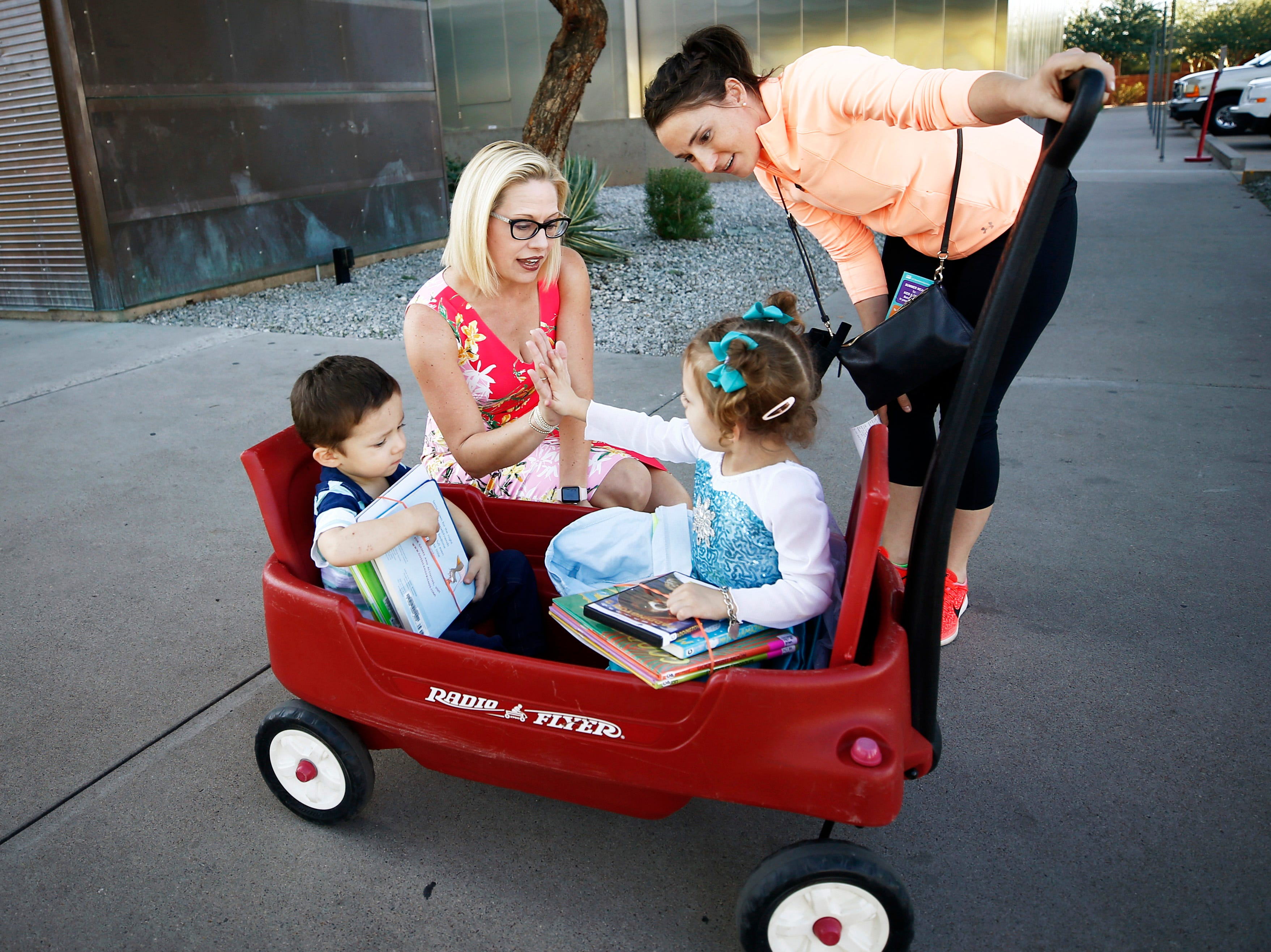 Rep. Kyrsten Sinema, D-Ariz., the Democratic candidate for Arizona's U.S. Senate seat greets Leanna Huerta and her children Xavier and Alexandreia outside a polling center on Nov. 6, 2018 at the Burton Barr Central Library in Phoenix.