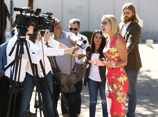 Rep. Kyrsten Sinema, D-Ariz., the Democratic candidate for Arizona's U.S. Senate seat, talks to the media outside a polling center on Nov. 6, 2018 at the Burton Barr Central Library in Phoenix.