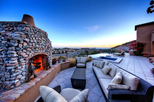 This Spanish style Paradise Valley home sits on a 1.3-acre hillside lot and includes a negative edge lap pool, tiled spa, and a custom stone fireplace.