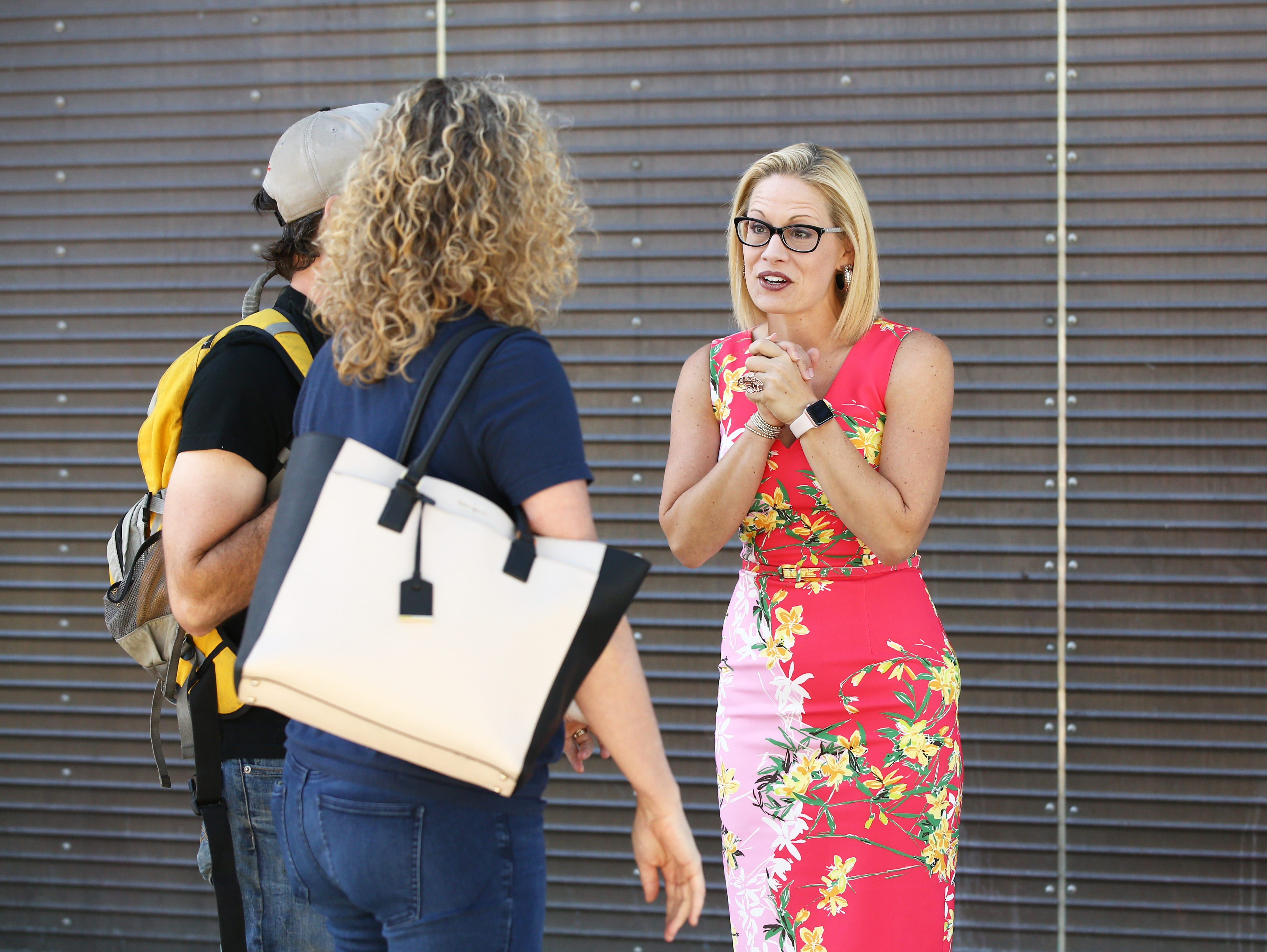 Rep. Kyrsten Sinema, D-Ariz., the Democratic candidate for Arizona's U.S. Senate seat, thanks a couple for voting outside a polling center on Nov. 6, 2018 at the Burton Barr Central Library in Phoenix.