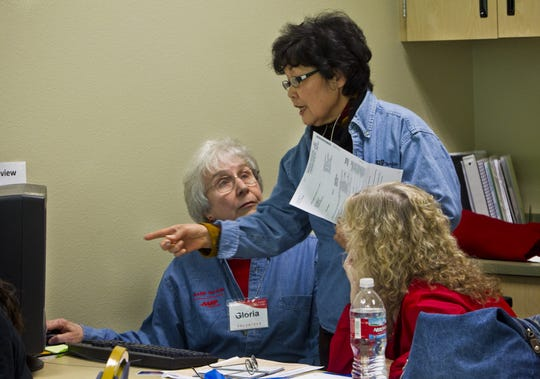 Kim Shin (center) answers a question from Tax-Aide volunteer Gloria Titus (left) as she helps prepare federal and state tax forms for Glendale resident Pat Ryan on Feb. 2, 2011. Shin is a retired nurse and Titus is a retired commercial tax preparer.