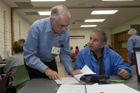 Tax-Aide volunteer Roy Lieber (left) assists Ray Rahim of Phoenix with his taxes at the Sunnyslope Senior Center in Phoenix.